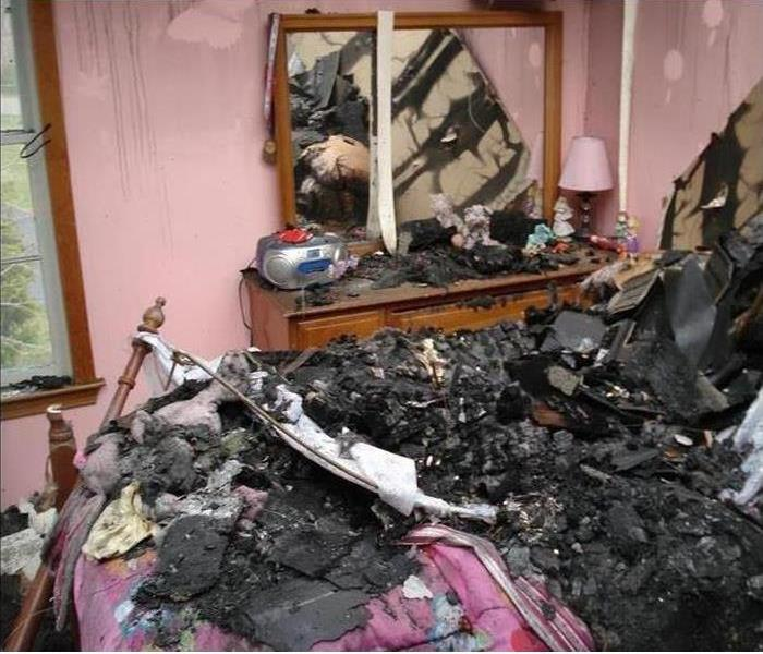 bedroom full of fire damaged debris