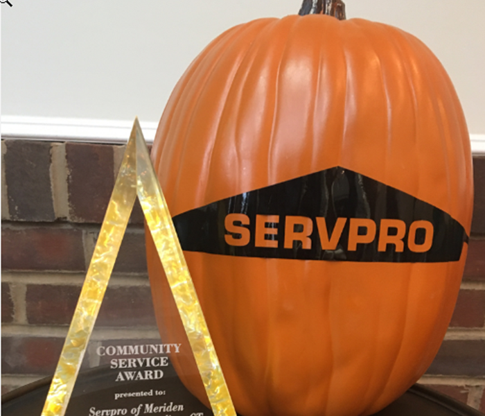 Pumpkin with SERVPRO logo on table next to award