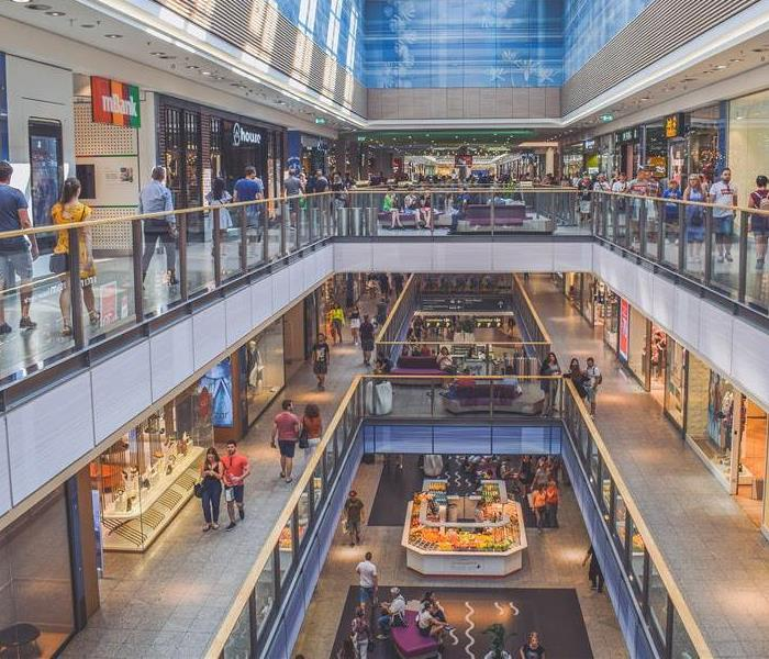 Looking down at multiple floors of a mall with people walking by the shops on every floor