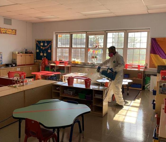 worker in full PPE disinfecting meriden classroom by fogging a sanitizer into air